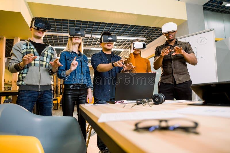 Team van ontwikkelaars die met virtuele werkelijkheidsglazen tijdens een commerci?le vergadering werken Jonge bedrijfscollega's stock foto's