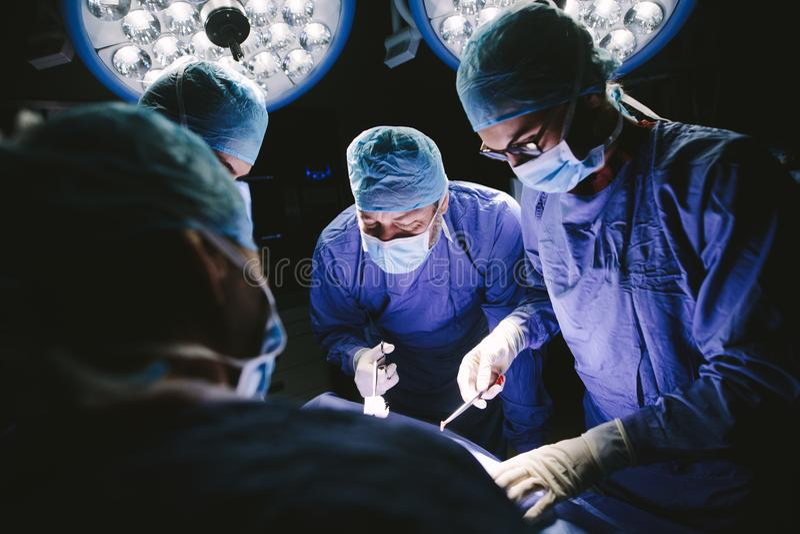 Team van professionele chirurgen die chirurgie uitvoeren stock afbeeldingen