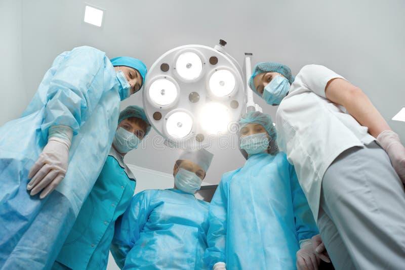 Team van professionele chirurgen die samen stellen stock afbeeldingen