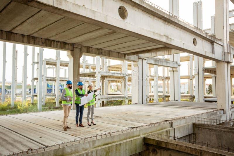 Team van succesvolle architecten en partners die vorderingen in het werk controleren op een bouwwerf royalty-vrije stock fotografie