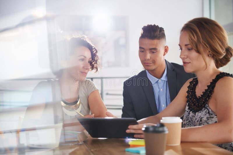 Team van succesvolle bedrijfsmensen die een vergadering in uitvoerend zonovergoten bureau hebben royalty-vrije stock afbeelding