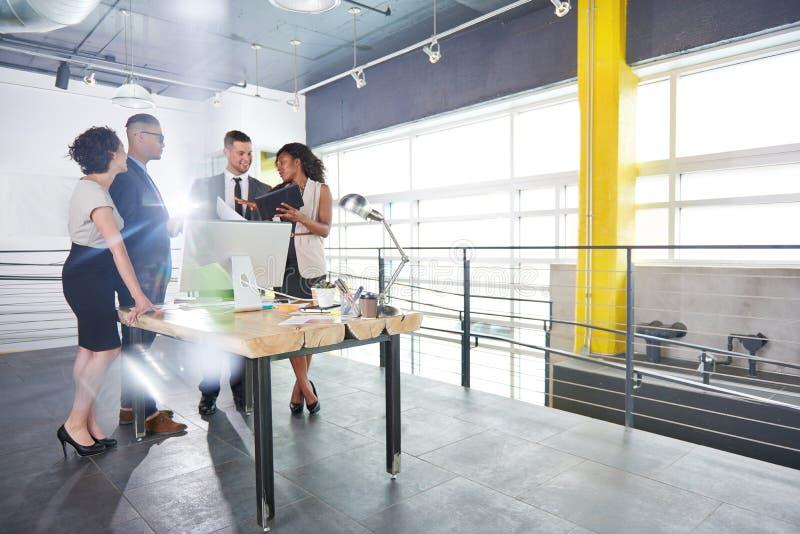 Team van succesvolle bedrijfsmensen die een vergadering in uitvoerend zonovergoten bureau hebben royalty-vrije stock foto's