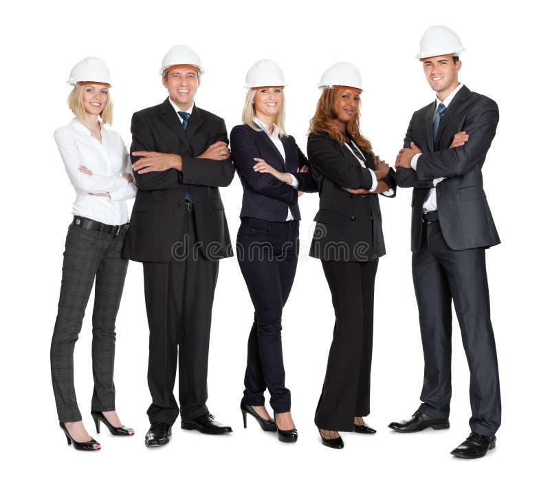 Team van succesvolle bouwvakkers op wit stock foto's