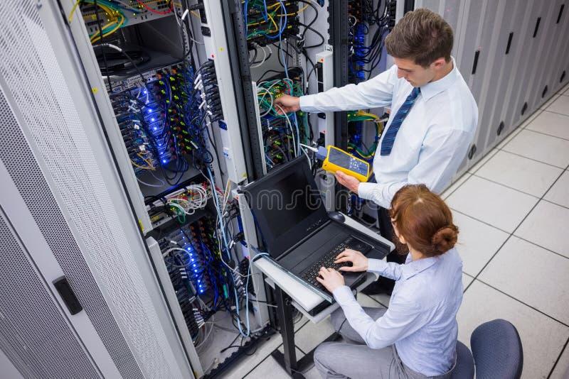Team van technici die digitale kabelanalisator op servers gebruiken royalty-vrije stock afbeelding