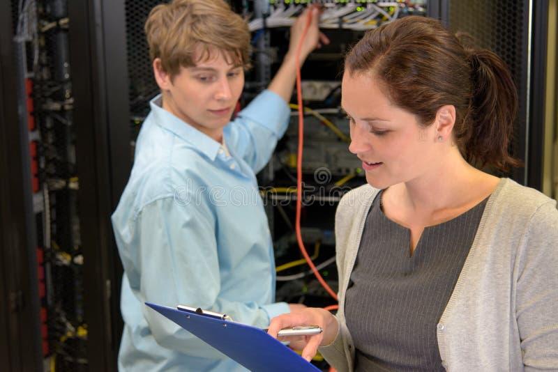 Team van IT technici in serverruimte stock fotografie