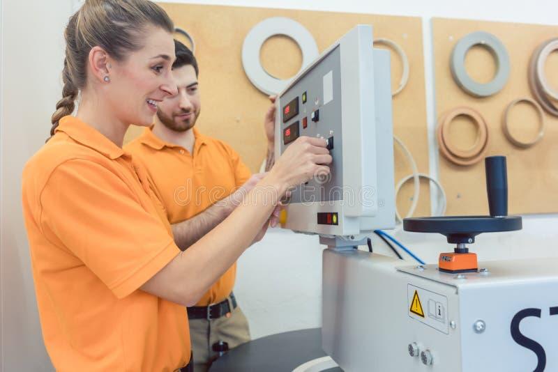 Team van timmerlieden die CNC machine in hun workshop programmeren stock foto's