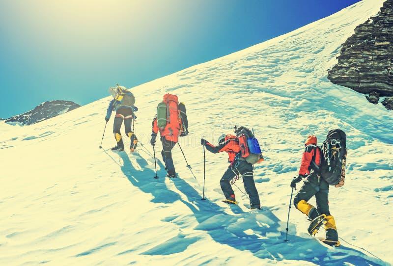 Team van vier alpinisten die een berg beklimmen royalty-vrije stock fotografie