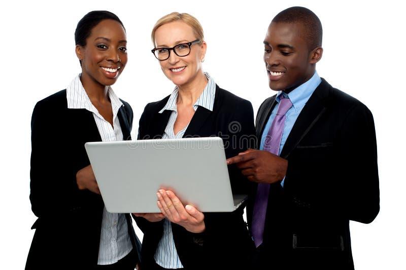 Team van vriendschappelijke bedrijfsmensen die laptop met behulp van royalty-vrije stock fotografie