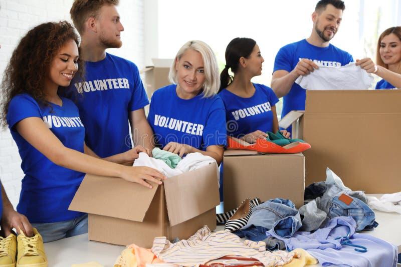 Team van vrijwilligers die schenkingen in dozen verzamelen stock foto