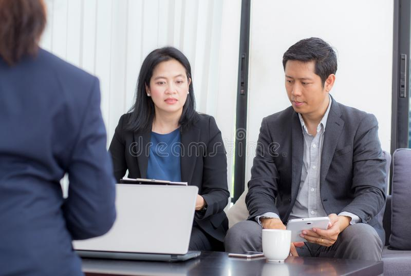 Team van zaken drie mensen die aan laptop met tijdens een vergaderingszitting rond een lijst samenwerken royalty-vrije stock foto's