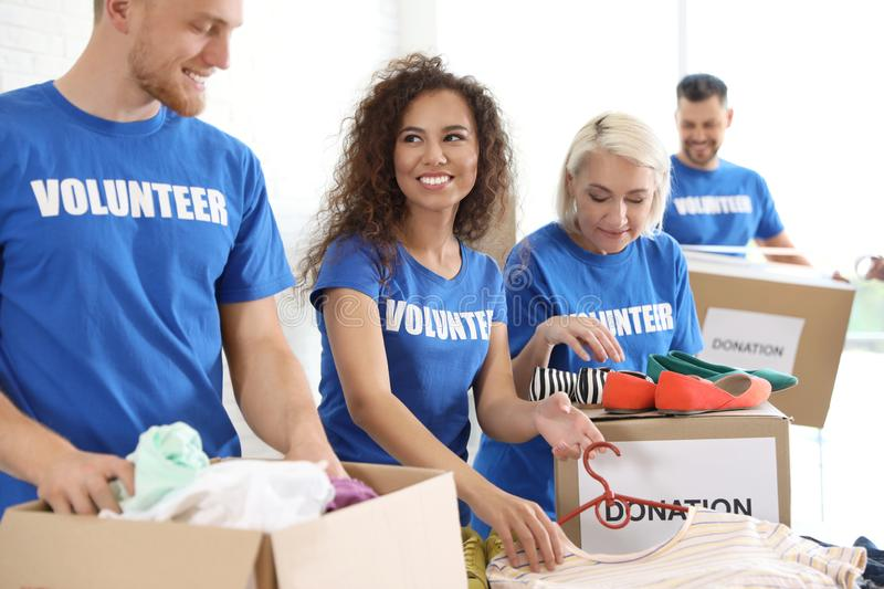 Team of volunteers collecting donations in boxes royalty free stock images