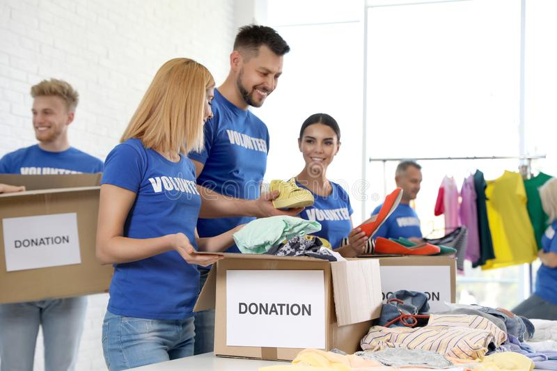 Team of volunteers collecting donations in boxes royalty free stock photography