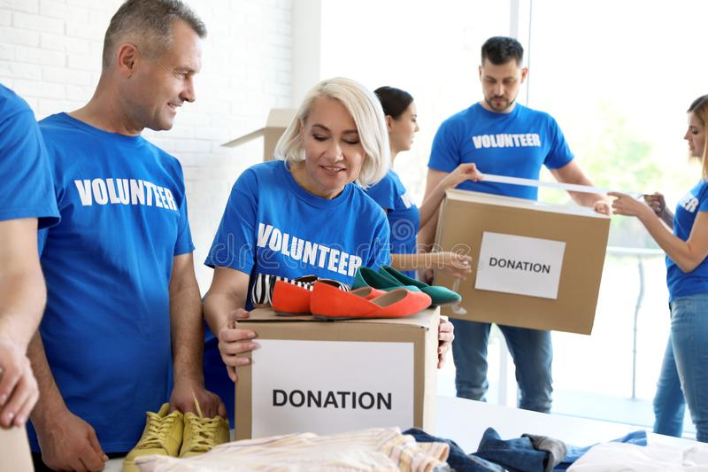 Team of volunteers collecting donations in boxes royalty free stock image