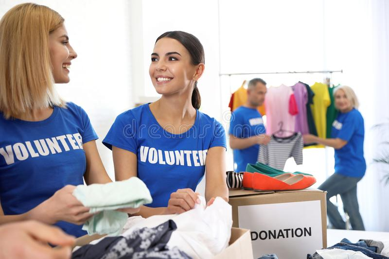 Team of volunteers collecting donations in boxes stock photo