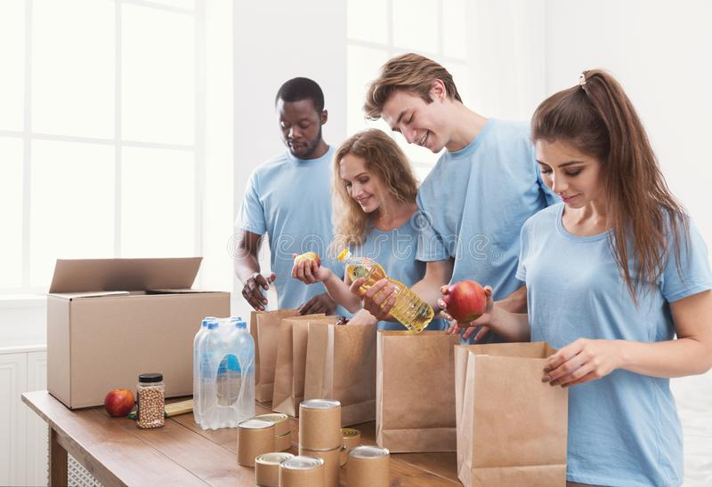 Volunteers packing food and drinks into paper bags stock photography
