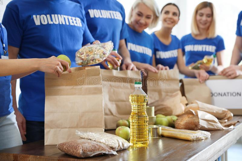 Team of volunteers collecting food donations at table stock photo