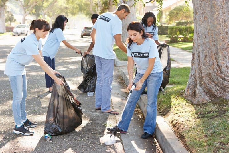 Team Of Volunteers Picking Up Litter In Suburban Street stock image