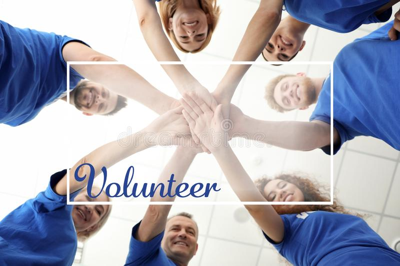 Team of volunteers putting their hands together on background, bottom view stock images