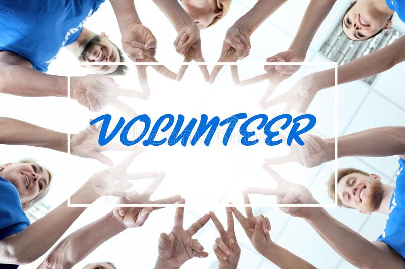 Team of volunteers putting their hands together on background, bottom view royalty free stock image