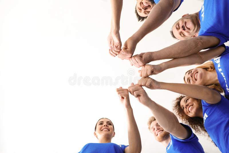 Team of volunteers putting their hands together on light background, bottom view stock image