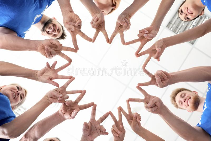 Team of volunteers putting their hands together on light background stock photography
