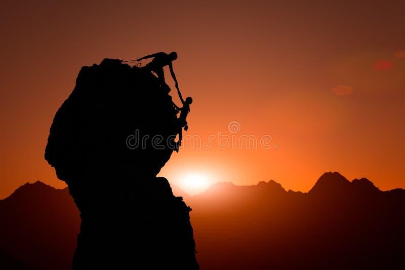 Team von Bergsteigern helfen, den Gipfel bei Sonnenuntergang zu erobern stockbilder