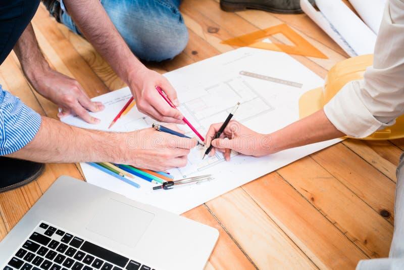 Team von den Architekten, die auf Boden mit Bau sitzen, plant lizenzfreie stockfotos