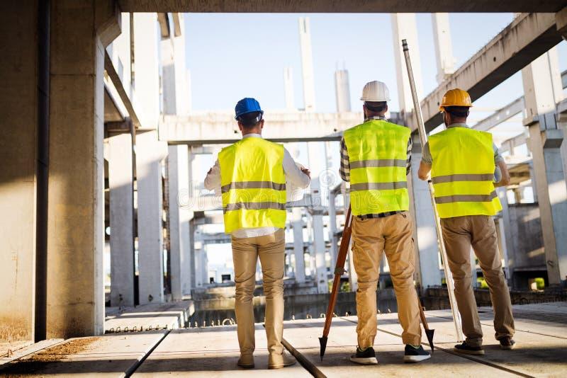 Team von den Bauingenieuren, die an Baustelle arbeiten stockfotos