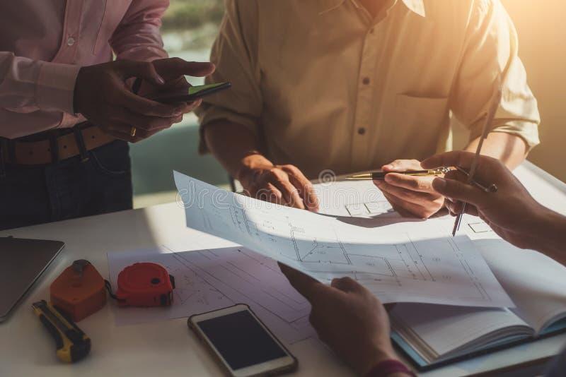 Team von den Berufsarchitekten, die Bauplanprojektplanung mit Plänen und Technikwerkzeugen im Konstruktionsbüro Arbeits sind stockbild