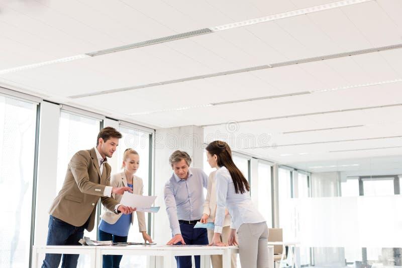 Team von den Geschäftsleuten, die Diskussion bei Tisch im neuen Büro haben lizenzfreie stockfotografie
