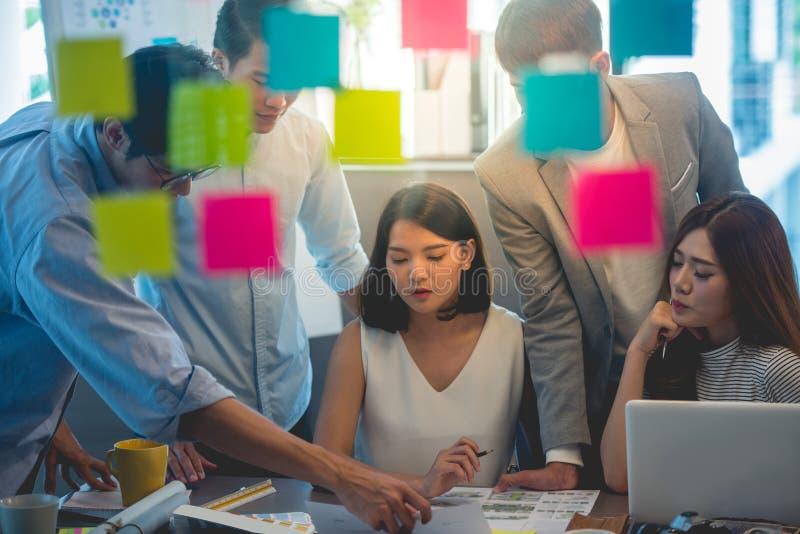 Team von den jungen Geschäftsangestellten, die auf der Schaffung von Darstellung im Büro zusammenarbeiten lizenzfreie stockfotos