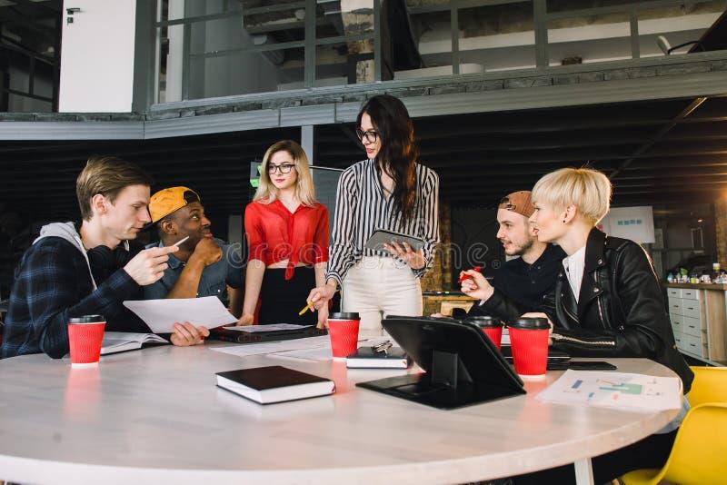 Team von den jungen Geschäftsfachleuten, die Technologie in einer informellen Sitzung engagiert auf Architektenentwurf einsetzen  stockbild
