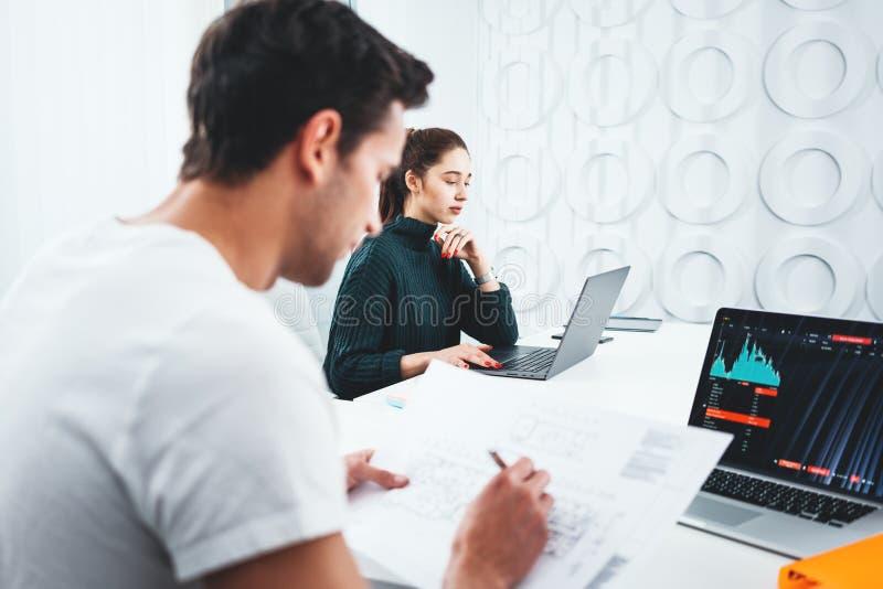Team von den jungen Mitarbeitern, die neue Geschäftsideen treffen und gedanklich lösen, benutzt modernen Laptop stockfotografie