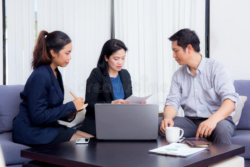 Team von den Leuten des Geschäfts drei, die zusammen an einem Laptop arbeiten stockfotografie