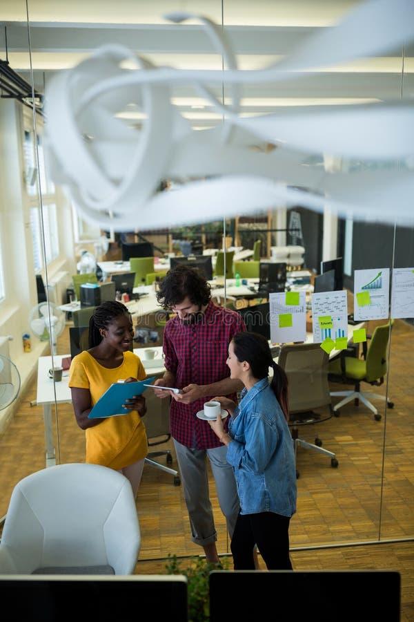 Team von den Unternehmensleitern, die über digitaler Tablette sich besprechen lizenzfreie stockfotografie