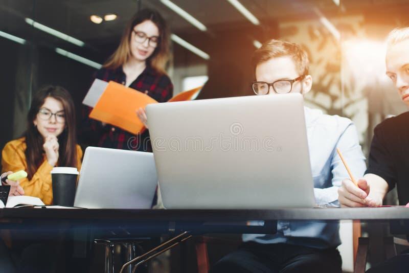 Team von Designern sitzt an einem Holztisch in einem modernen Büro und lizenzfreie stockbilder