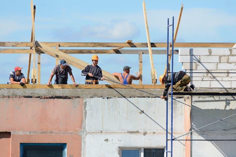 Team von Erbauern baut Baugerüst für Bauarbeit zusammen stockbilder