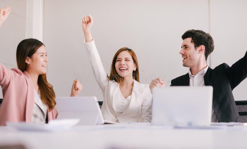 Team von erfolgreichen Geschäftsleuten feiert das Empfangen der positiven Antwort von den Investoren stockfotografie