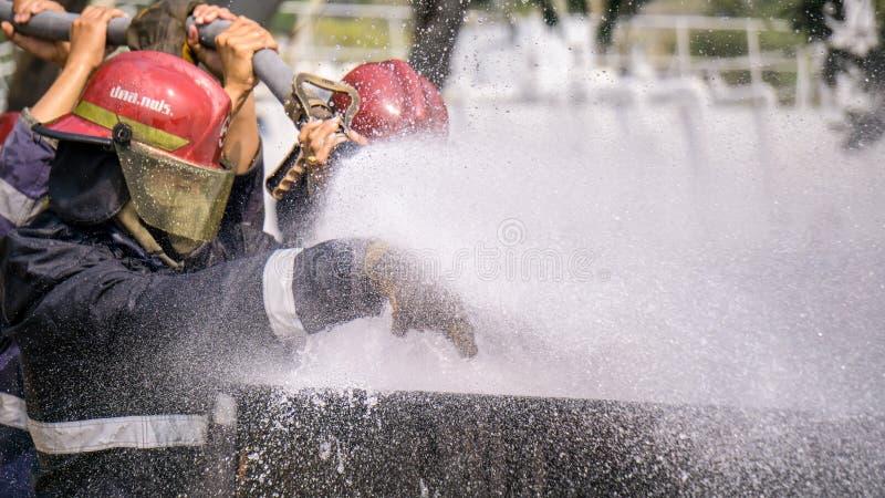 Team von Feuerbekämpfungsauszubildenden löschen enormes Feuer mit Wasser aus stockbilder