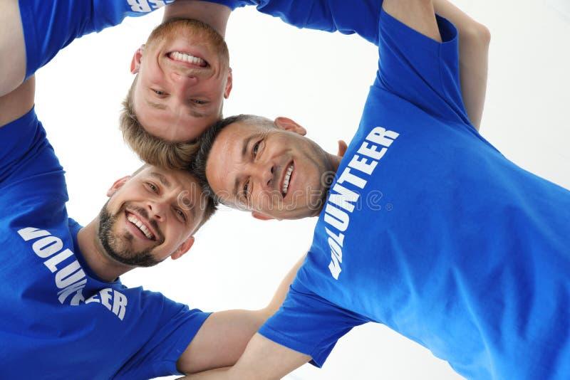 Team von Freiwilligen schloss sich Kreis auf heller, Ansicht von unten an stockfoto