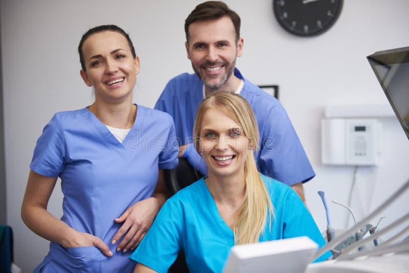 Team von gl?cklichen stomatologists in der Klinik des Zahnarztes stockbild