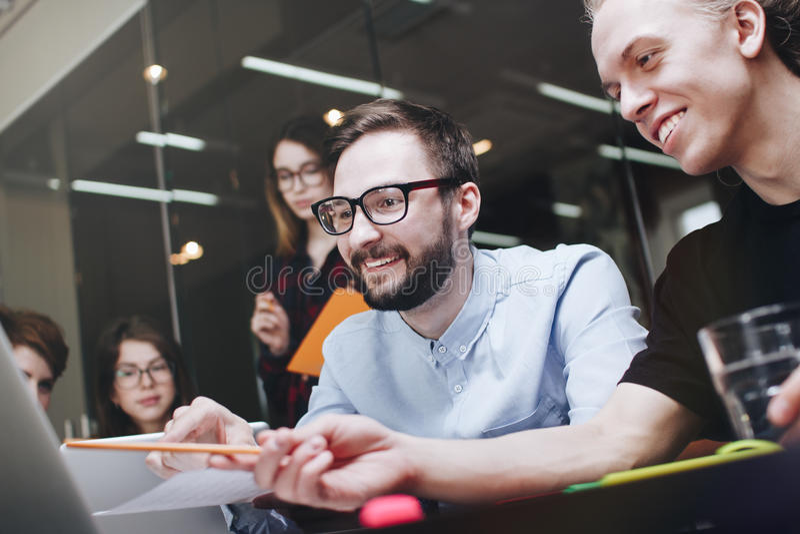 Team von netten Kollegen arbeitet an modernen Geräten Mannschaft von den Mitarbeitern, die Arbeitssitzung im Dachbodenbüro machen lizenzfreies stockfoto
