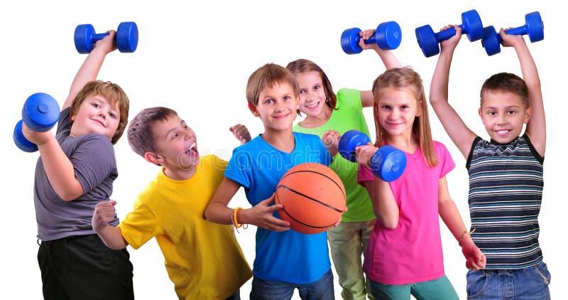 Team von sportiven Kinderfreunden mit Dummköpfen und Ball stockbild