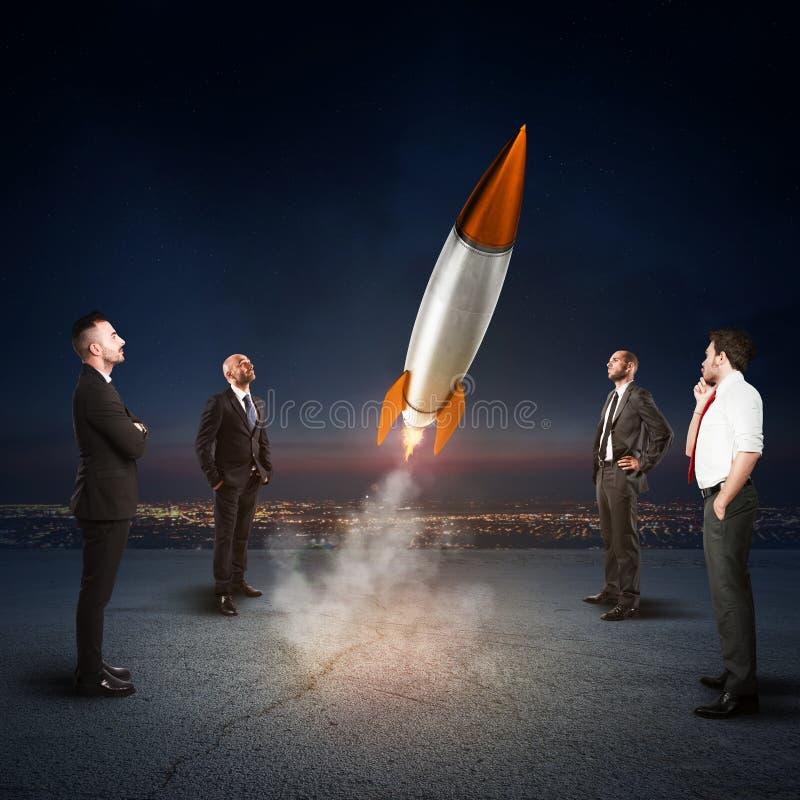 Team von Wirtschaftlerblicken stellen eine Rakete an Konzept des Firmenstarts und des neuen Geschäfts Wiedergabe 3d lizenzfreies stockfoto