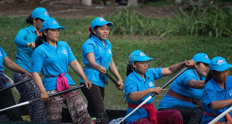 SIEM REAP, CAMBODIA - NOVEMBER, 2016: Team of women boat racers rest as they glide past the finish line stock photos