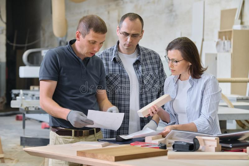 Team of woodworking workshop workers are discussing. Group of people client, designer or engineer and workers discuss work royalty free stock image