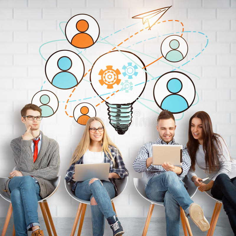 Team work concept. Cheerful young european team sitting on chairs and using laptops in brick interior with creative sketch on wall. Team work concept royalty free stock images