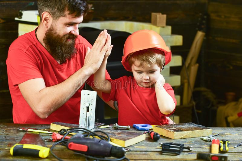Team work concept. Father with beard teaching little son to use tools in classroom, chalkboard on background. Boy, child royalty free stock image