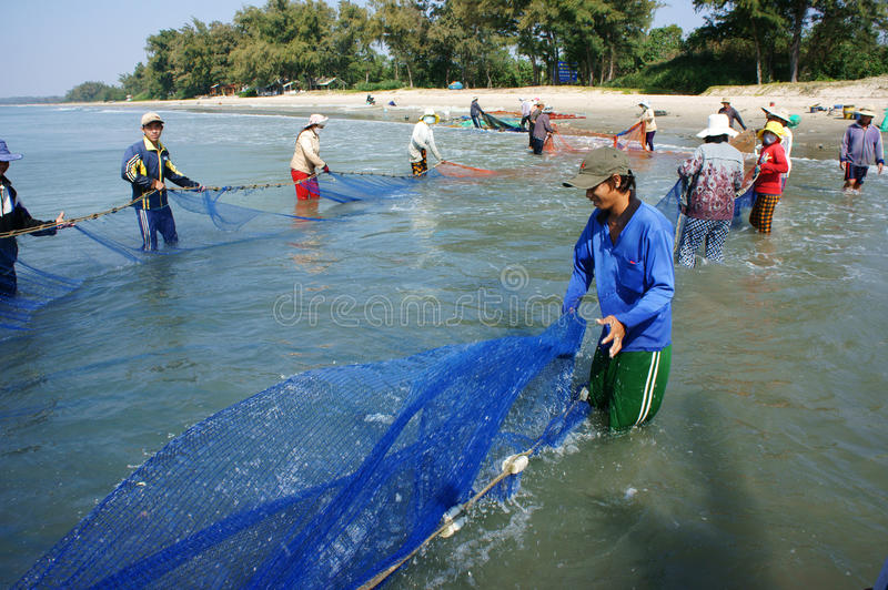 Team work of fisherman on beach stock images