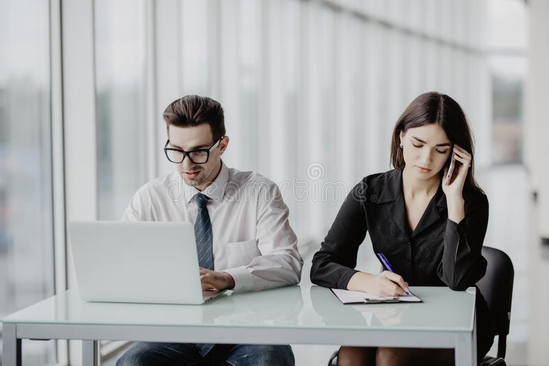 Team Work. Handsome Business Man Working On Laptop While Business Woman  Making Phone Call In Modern Office Stock Photo - Image of businessman,  lifestyle: 102301462